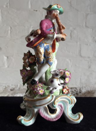 Bow figure of a shepherd playing a flute, a dog at his feet, c.1760-0