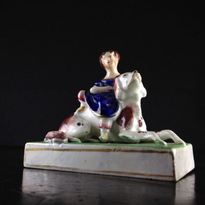 Staffordshire porcelain of a child seated on a dog,  circa 1825-45. -5440
