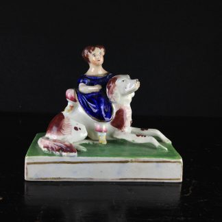 Staffordshire porcelain of a child seated on a dog,  circa 1825-45. -0