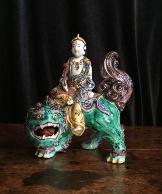 Japanese porcelain figure of Kannon (Guanyin) on a shishi (Foo dog), in famille verte colours, c.1890-0