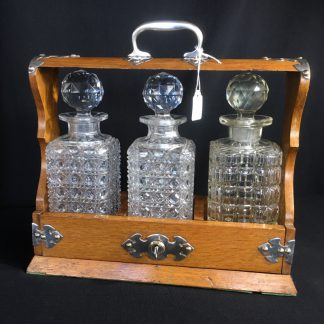 Oak three decanter tantalus, plated mounts, c.1885-0