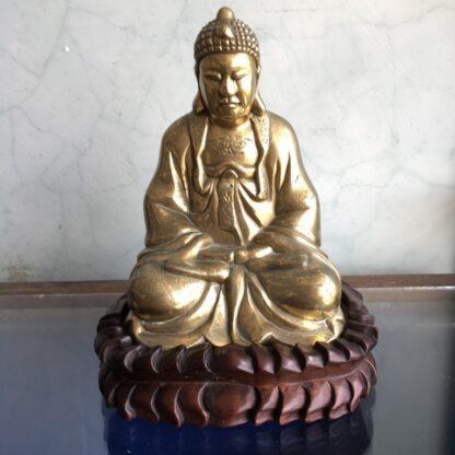 Oriental sitting brass Buddha on carved stand, C. 1900-0